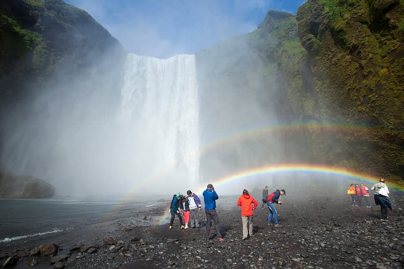 Tourists in the rainbow beneath 60m-high Skogafoss waterfall, Skogar, Sudhurland, Iceland.