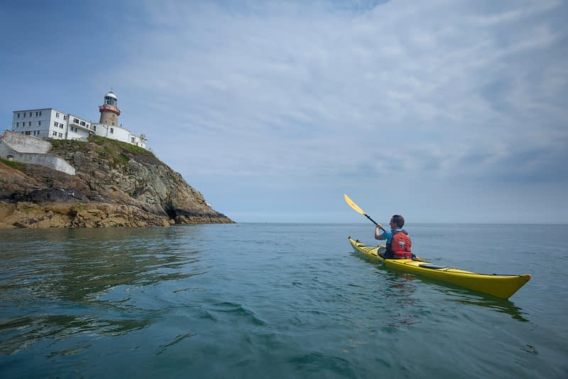 Sea kayaker beneath Baily Lighthouse, Howth Head, County Dublin, Ireland.