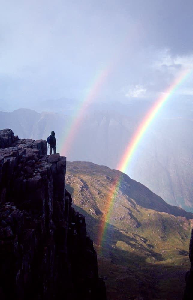 Walker and rainbow, Bidean nam Bian, Glencoe, Scotland.