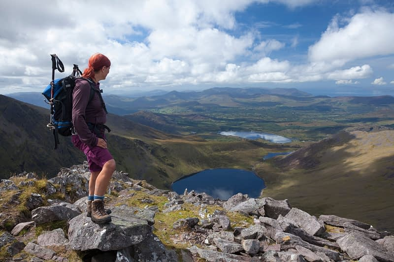 Hiker looking over Coomloughra Lough from Beenkeragh, MacGillycuddy's Reeks, County Kerry, Ireland.