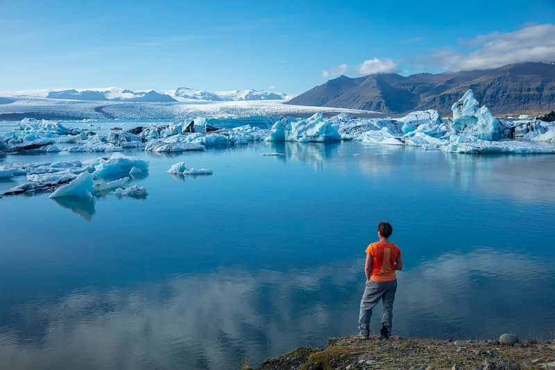 Person on the shore of Jokulsarlon glacier lagoon, beneath Vatnajokull glacier. Sudhurland, south east Iceland.