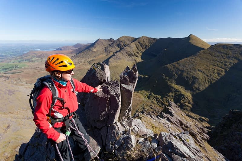 Rock climber and pinnacle on Howling Ridge, Carrauntoohil, MacGillycuddy's Reeks, County Kerry, Ireland.