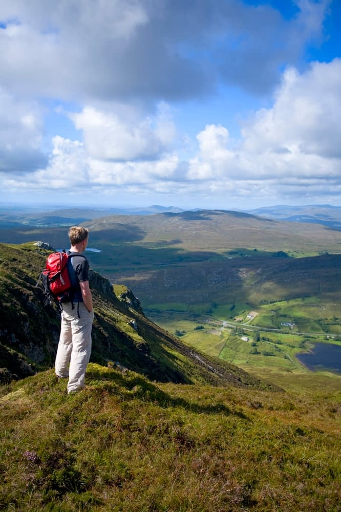 Walker looking over Lough Talt from Aghla Mountain, Co Donegal, Ireland.