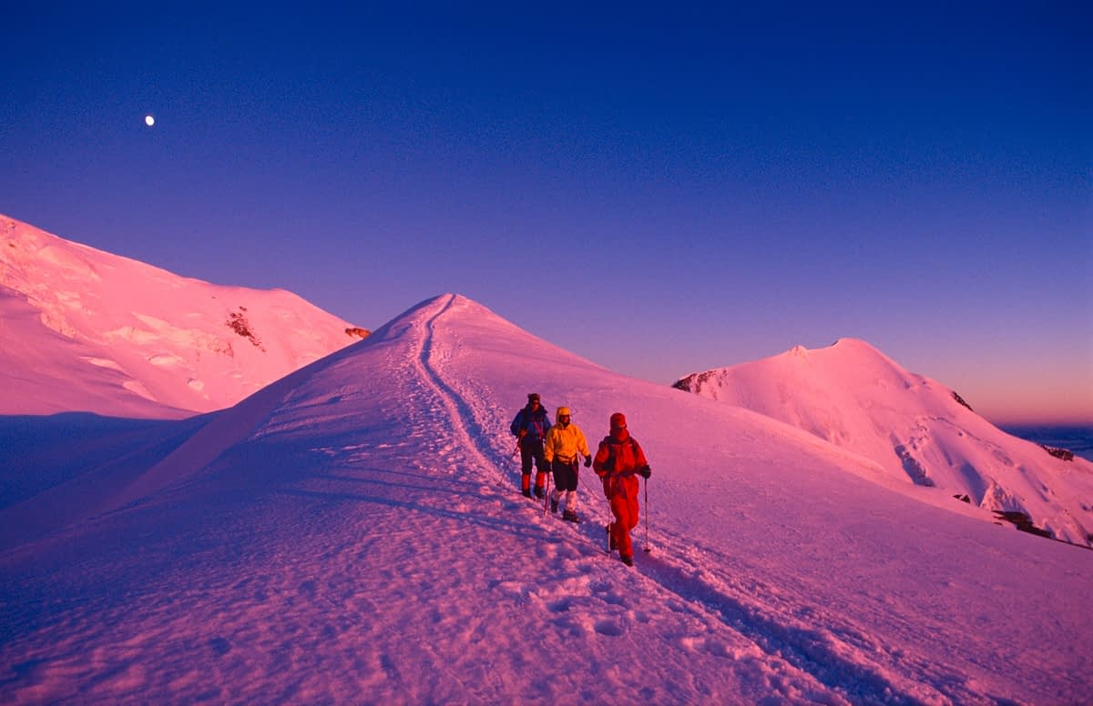 Mountaineers descending from Mont Blanc at sunset, French Alps, France.