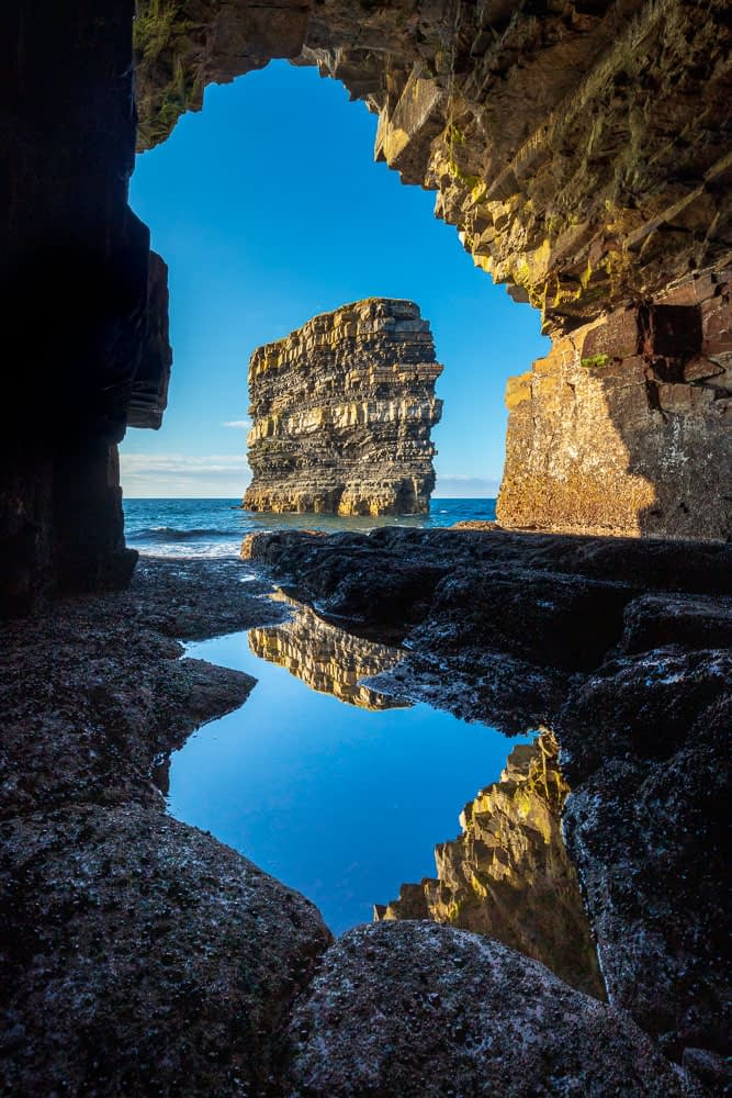 Dun Briste sea stack framed by a cave beneath Downpatrick Head. County Mayo, Ireland.