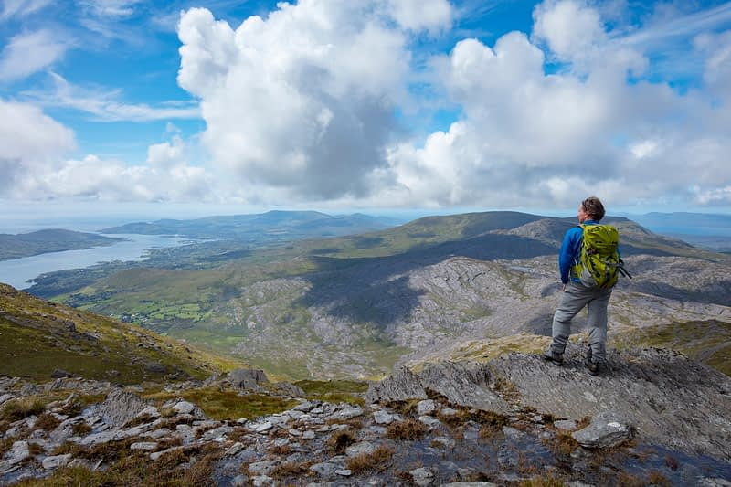 Hiker looking over the Beara Peninsula from the summit of Hungry Hill, County Cork, Ireland.