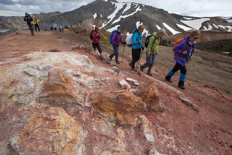 Hikers passing volcanic mineral deposits at Landmannalaugar, Sudhurland, Iceland.