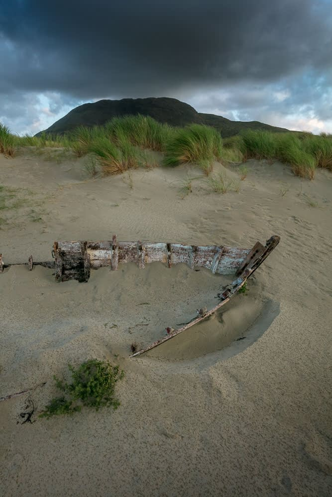 Carcass of a wrecked fishing boat on Glassilaun Beach, Connemara, County Galway, Ireland.