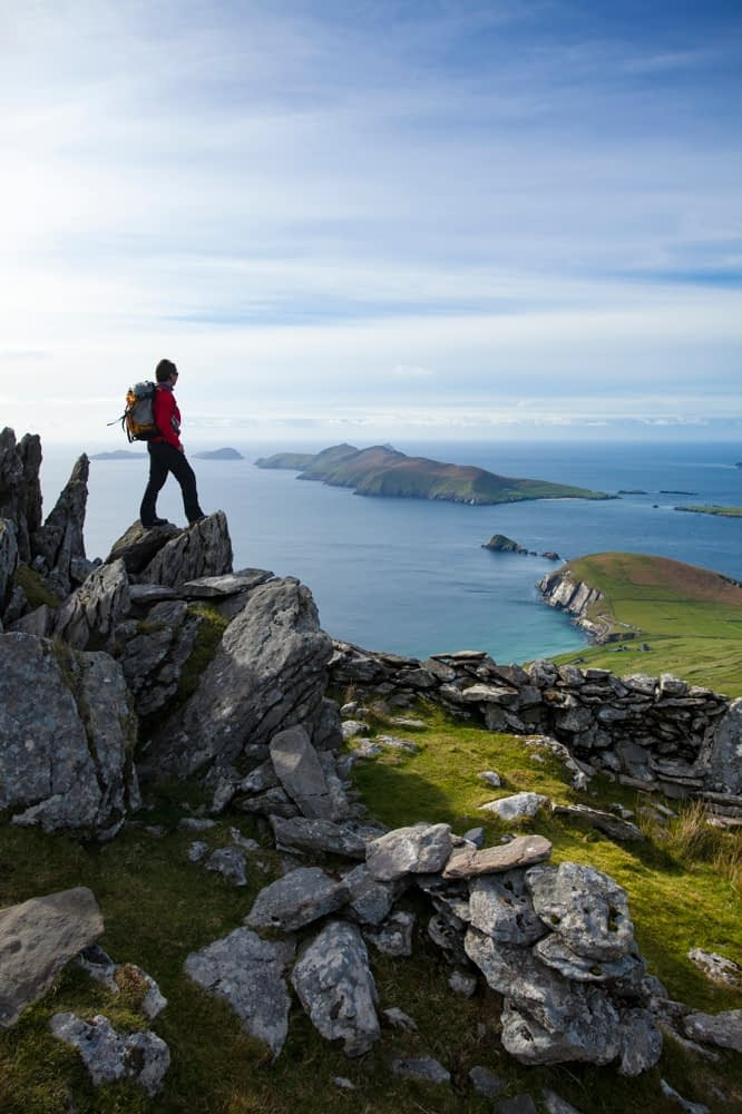 Walker looking across Slea Head and the Blasket Islands from Eagle Mountain, County Kerry, Ireland.