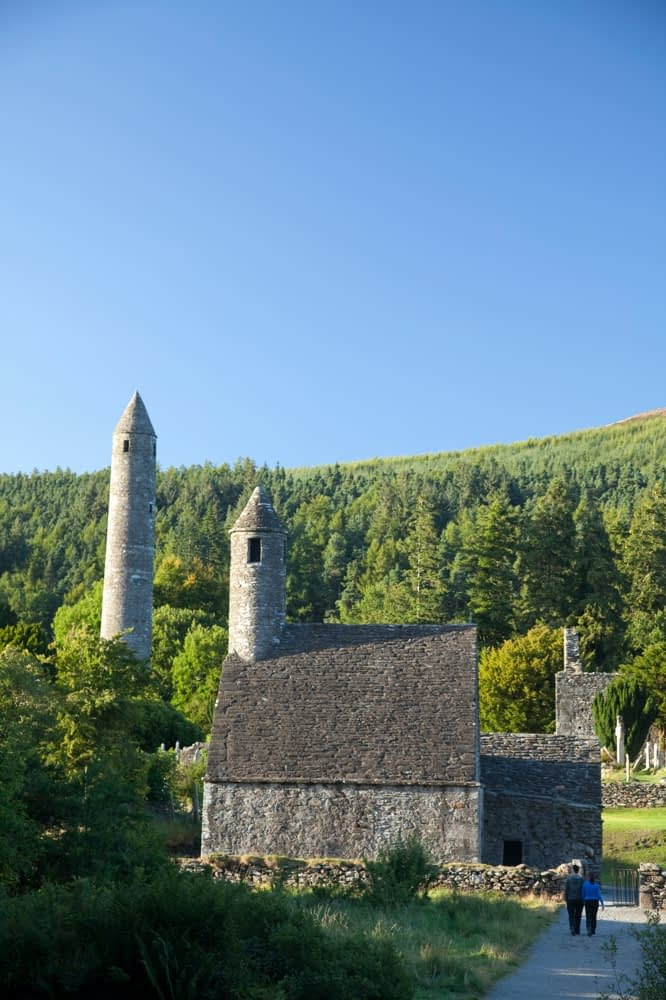 Visitors beneath St Kevin's church and round tower, Glendalough monastic site, Co Wicklow, Ireland.