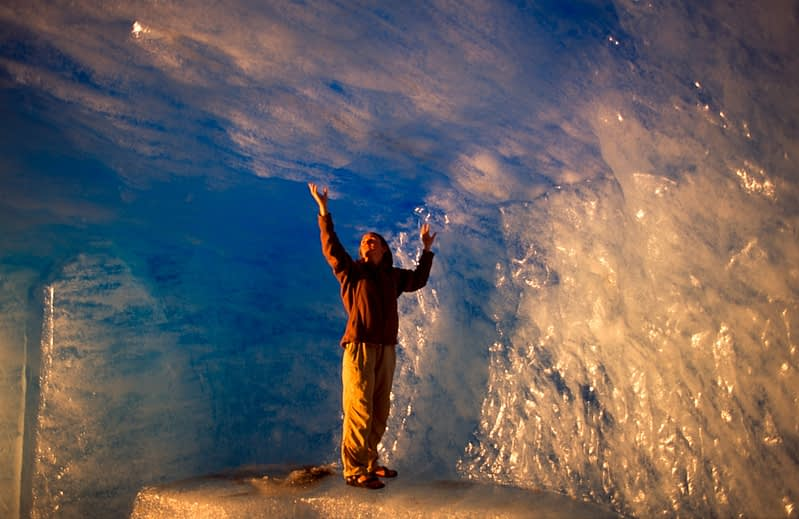 Person inside an ice cave in the Rhone glacier, Valais, Swiss Alps, Switzerland.