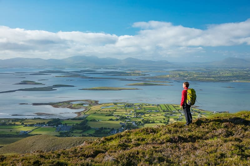 Hiker looking over Clew Bay from the slopes of Croagh Patrick, County Mayo, Ireland.