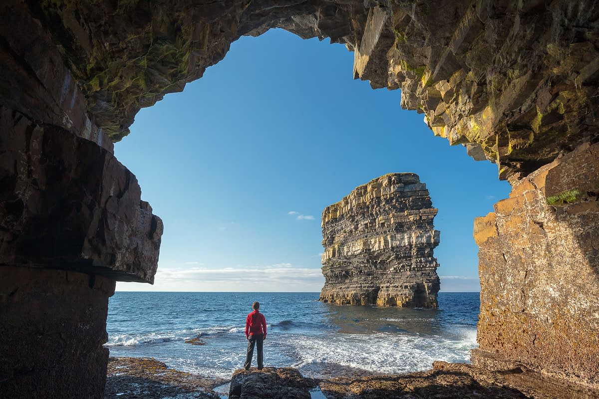 Person viewing Dun Briste sea stack from a cave beneath Downpatrick Head. County Mayo, Ireland.