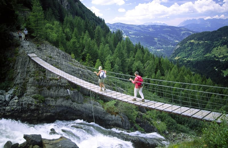 Walkers crossing a swing bridge over Torrent Bionnassay, Tour of Mont Blanc, French Alps, France.