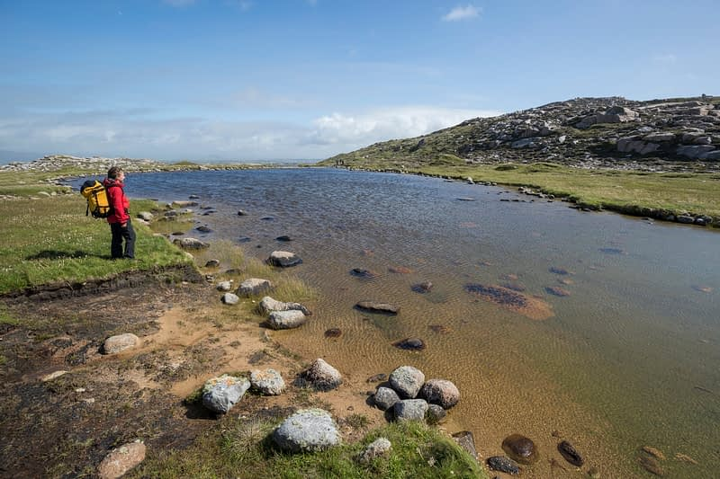 Hiker beside Owey Island lough, County Donegal, Ireland.