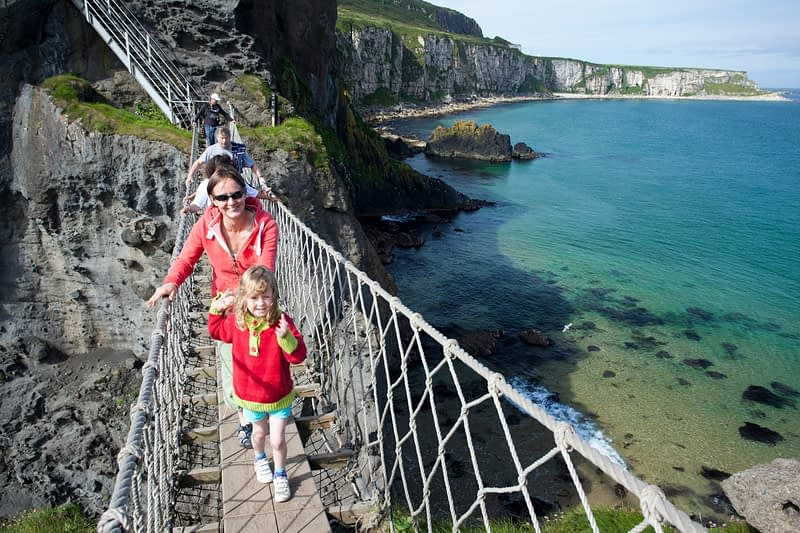 Woman and child crossing Carrick-a-rede Rope Bridge, County Antrim, Northern Ireland.