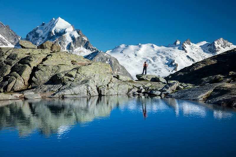 Reflection of hiker beneath Piz Rosbeg, Fuorcla Surlej, Berniner Alps, Graubunden, Switzerland.