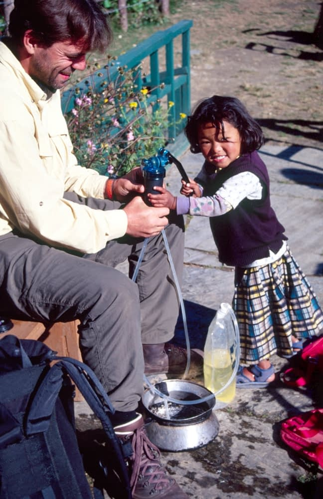 Trekker playing with a Nepali child, Annapurna Circuit, Nepal.