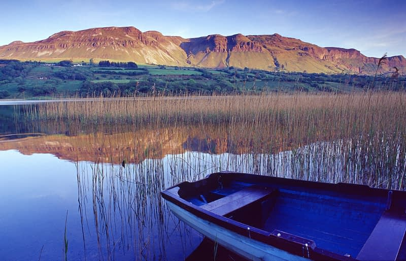 Boat and reflection of Castlegal Mountain in Glencar Lough, Co Sligo, Ireland.