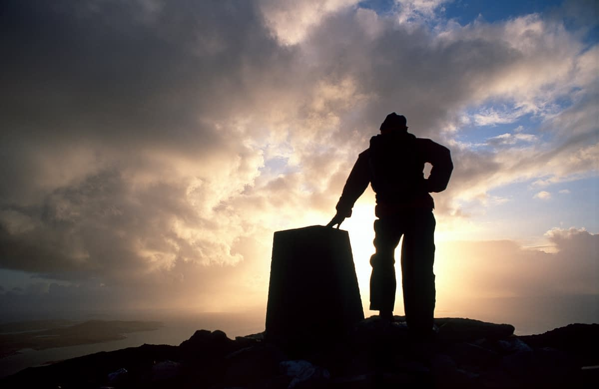 Walker at the summit of Tully Mountain, Connemara, County Galway, Ireland.