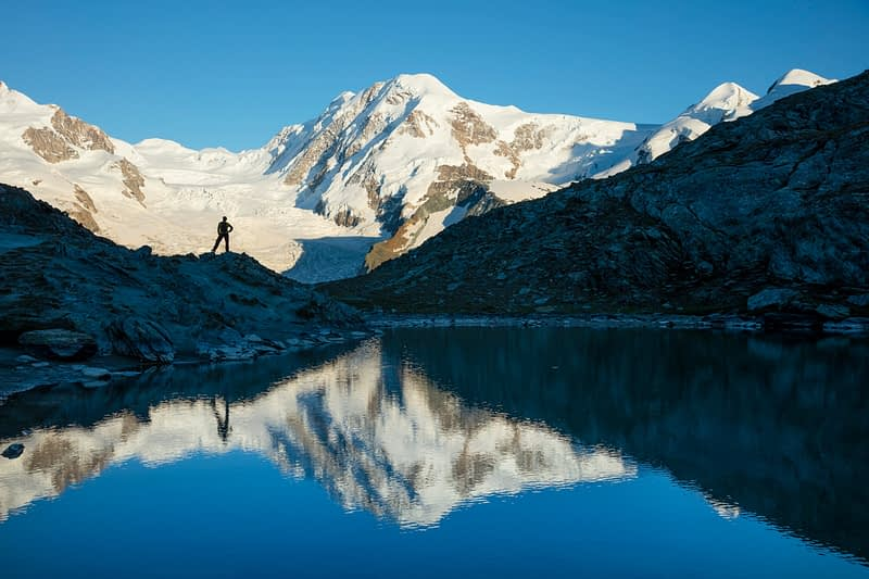 Hiker and Lyskamm reflected in the Riffelsee, Zermatt, Valais, Switzerland.