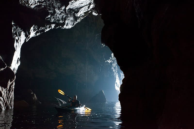 Sea kayaker in a cave beneath the Slieve League cliffs, County Donegal, Ireland.