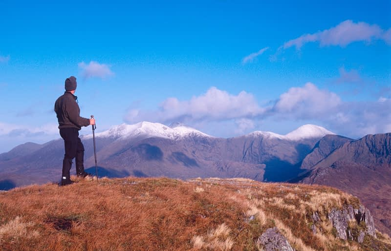 Walker looking to MacGillycuddy's Reeks from Mullaghanattin, Iveragh Peninsula, Co Kerry, Ireland.