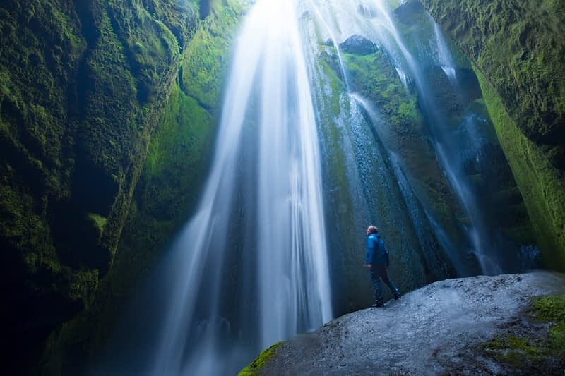 Person in the canyon beneath Gljufurarfossi waterfall, Seljaland, Sudhurland, Iceland.