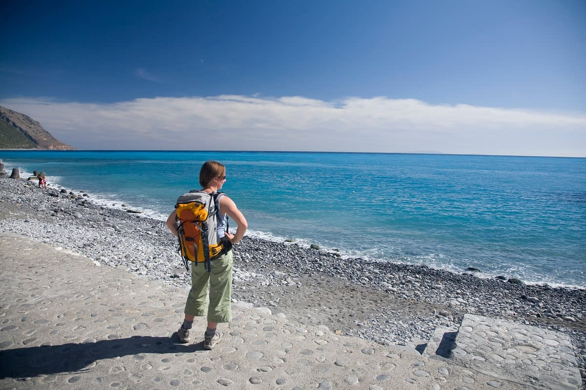 Hiker at the seafront in Agia Roumeli, base of the Samaria Gorge, Crete, Greece.