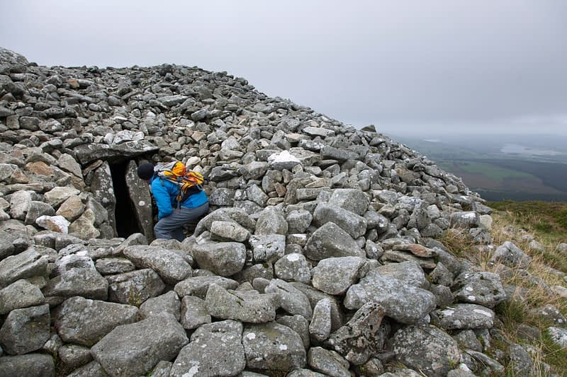 Walker and neolithic tomb at the summit of Seefin (621m), Wicklow Mountains, County Wicklow, Ireland.