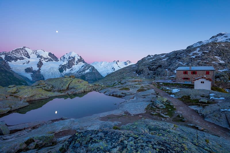 Moonrise over Piz Bernina and Fuorcla Surlej refuge, Berniner Alps, Graubunden, Switzerland.