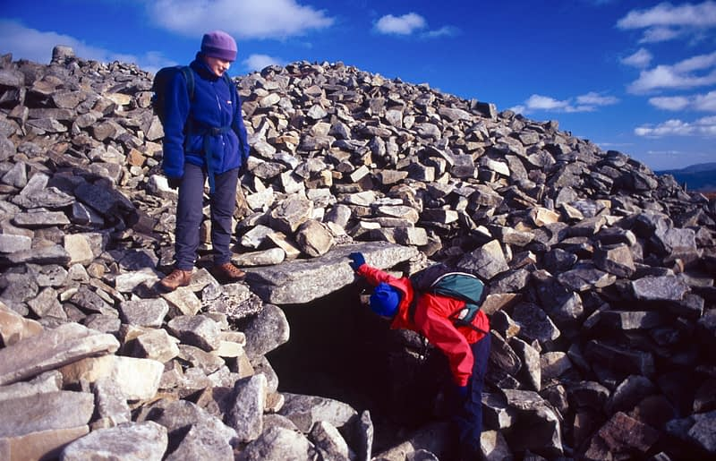 Walkers investigate a neolithic tomb at the summit of Slieve Gullion, Co Armagh, Northern Ireland.