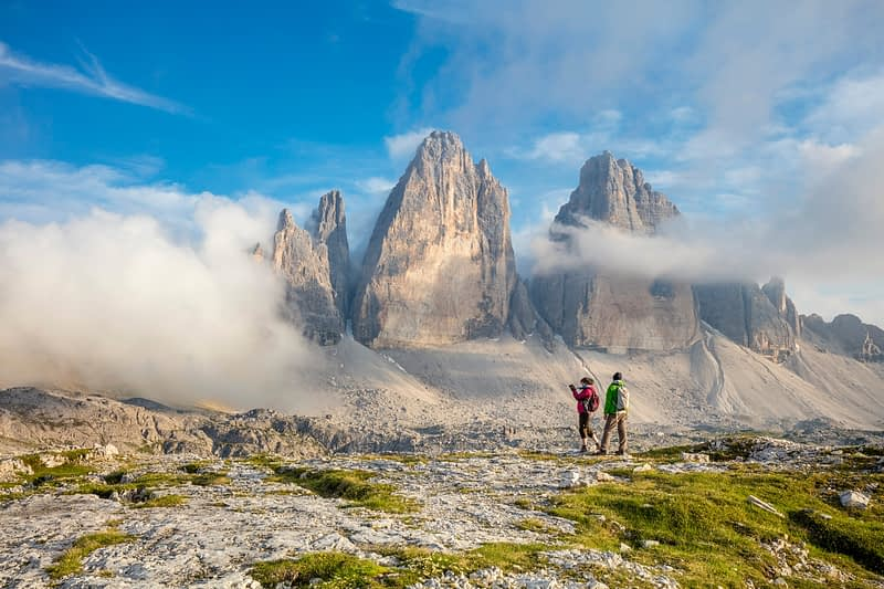 Hikers beneath Tre Cime di Lavaredo, Sexten Dolomites, South Tyrol, Italy.