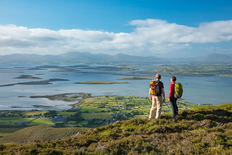 Hikers looking over Clew Bay from the slopes of Croagh Patrick, County Mayo, Ireland.