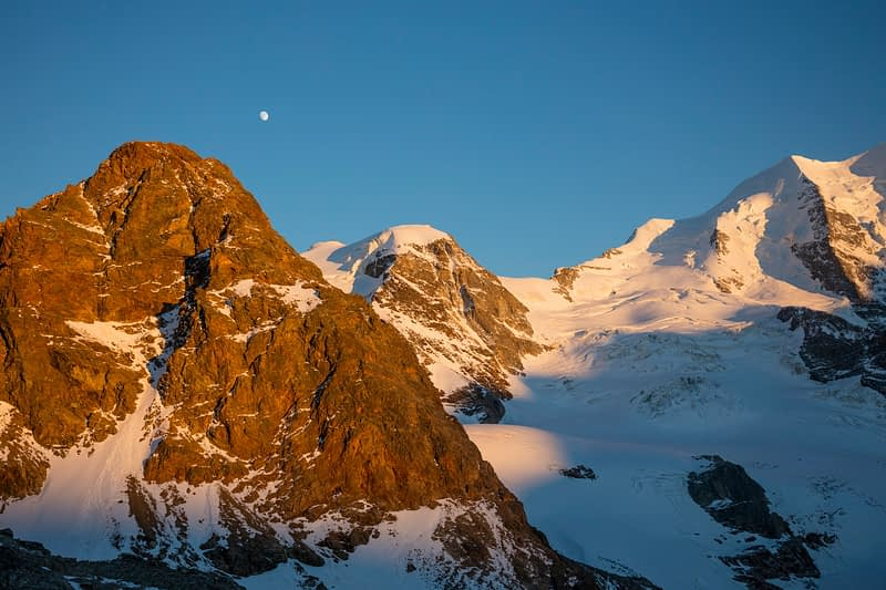 Evening moonrise over Piz Trovat, Berniner Alps, Graubunden, Switzerland.