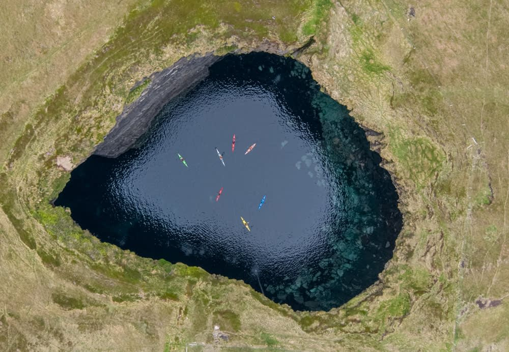 Aerial view of sea kayakers in a colapsed cave at Poladarky, County Mayo, Ireland.