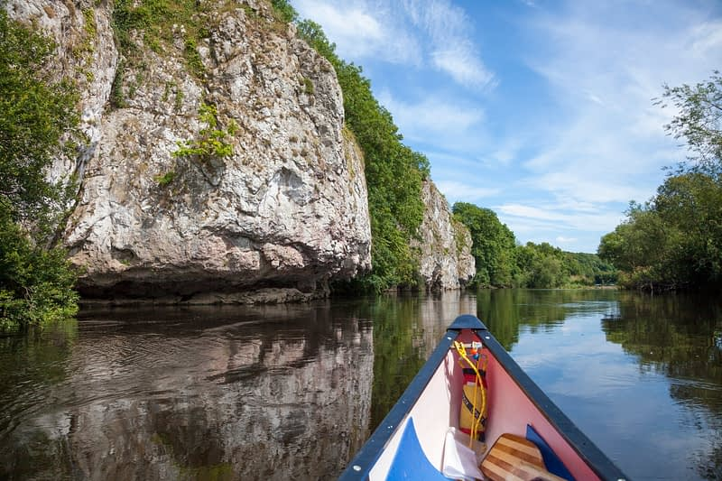 Canoeing beside limestone cliffs on the Blackwater River, Mallow, County Cork, Ireland.