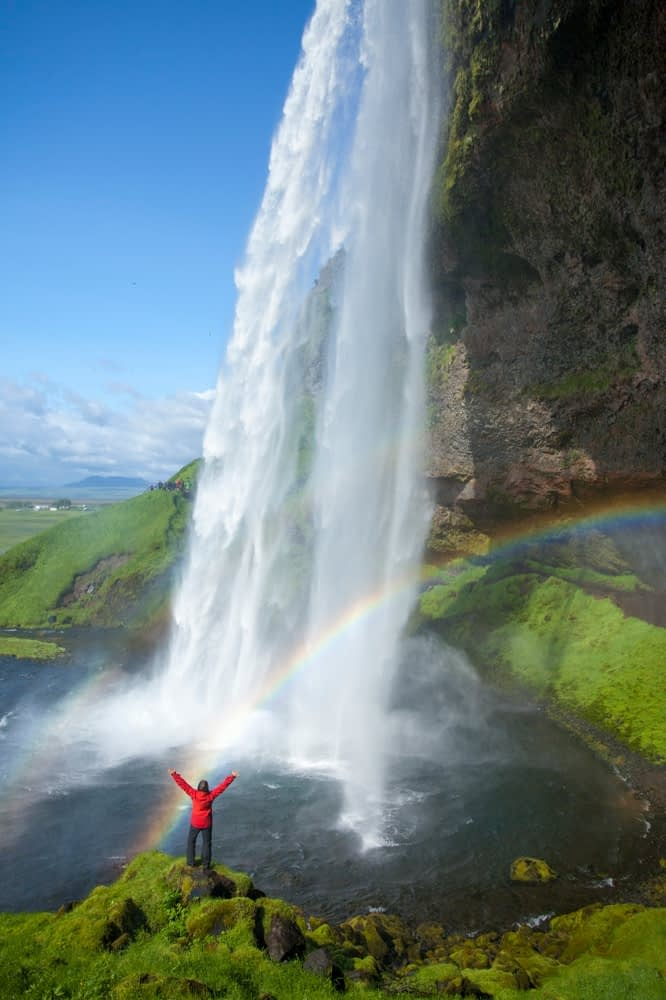 Person and rainbow beneath 60m-high Seljalandsfoss waterfall, Sudhurland, Iceland.