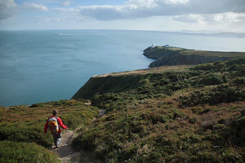 Walker heading towards Baily Lighthouse, Howth Coatal Path, County Dublin, Ireland.