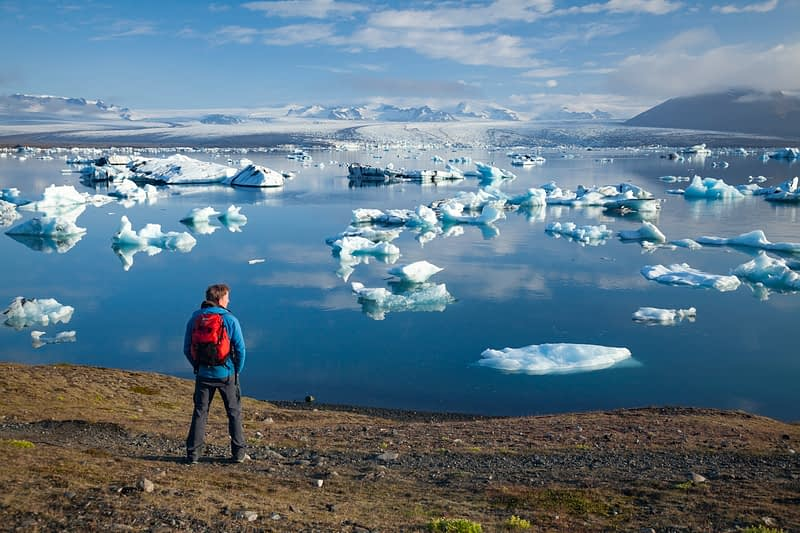 Hiker on the shore of Jokulsarlon iceberg lagoon, Sudhurland, Iceland.