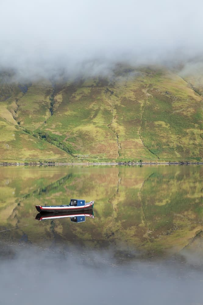 Reflection of mist and fishing boat, Killary Harbour, County Mayo, Ireland.