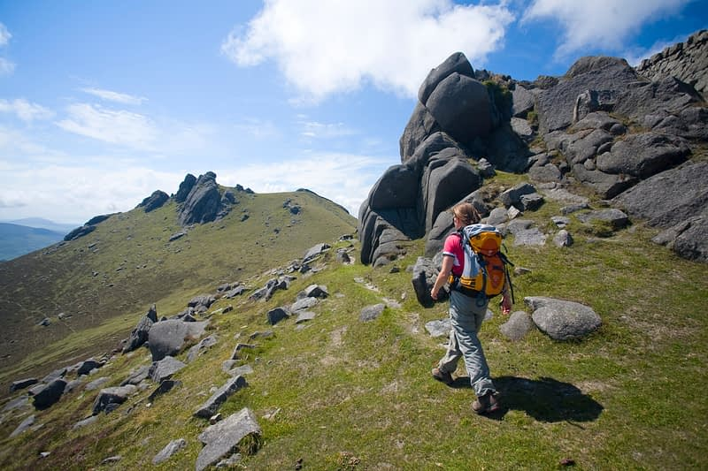 Walker passing the North Tor of Slieve Bearnagh, Mourne Mountains, Co Down, Northern Ireland.