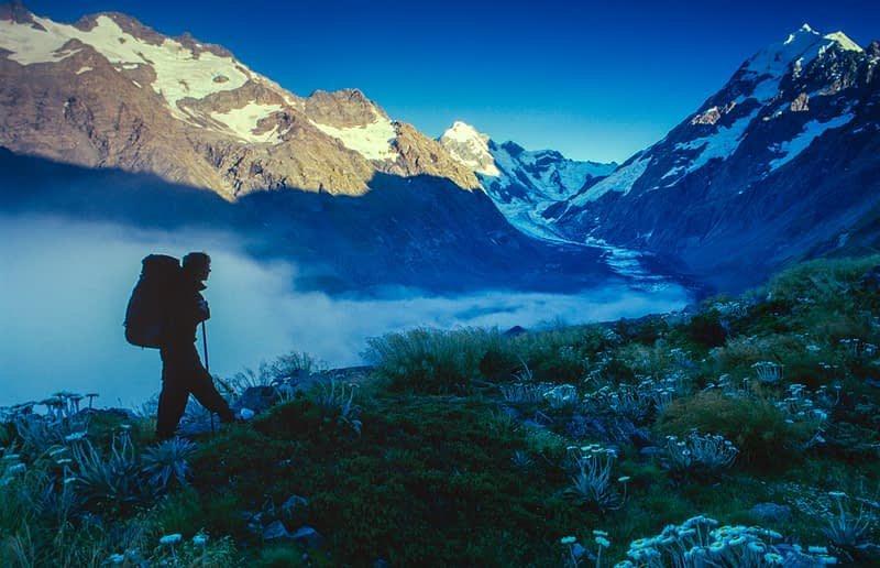Hiker silhouetted beneath Aoraki / Mt Cook, Mount Cook National Park, South Island, New Zealand.