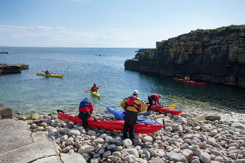 Sea kayakers launching from Inishmurray Island, County Sligo, Ireland.
