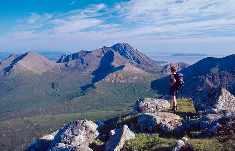 Walker looking towards Blaven from Beinn Dearg Mhor, Isle of Skye, Scotland.