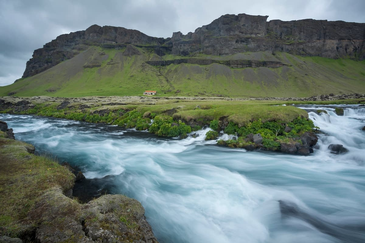 Cliffs and farmhouse beside the Odulbruara river, Brunasandur, Sudhurland, Iceland.