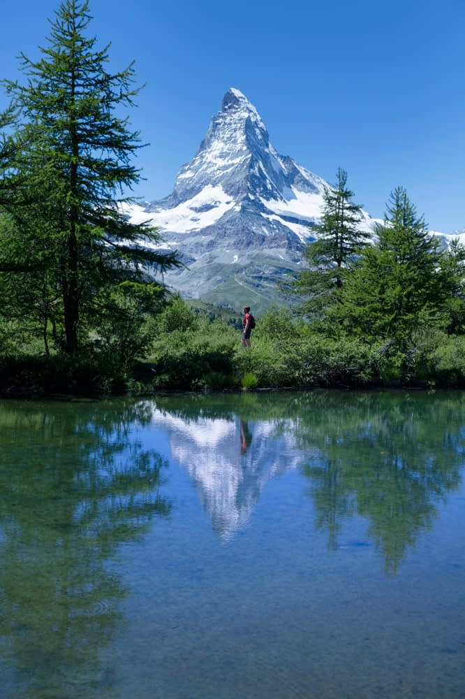 Hiker and Matterhorn reflected in the Grunsee, Zermatt, Valais, Switzerland.