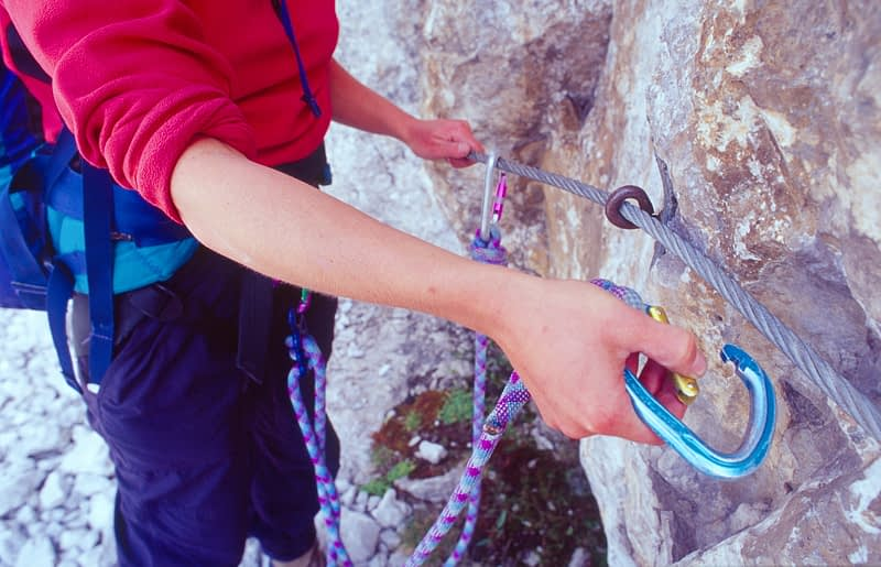 Climber clipping in to a via ferrata cable, Brenta Dolomites, Italian Alps, Italy.