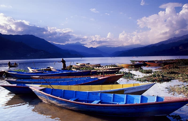 Wooden fishing boats on the shore of lake Phewa Tal, Pokhara, Nepal.