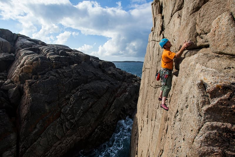 Iain Millar climbing a sea stack near Gwedore, County Donegal, Ireland.